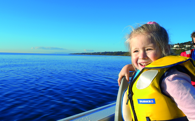 A young girl wearing a lifejacket on a boat