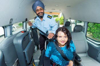 Image of woman being restrained in a Wheelchair Accessible Taxi.